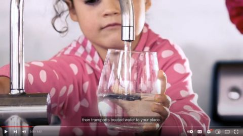 A screenshot from a video of a girl filling a glass with water from a tap.